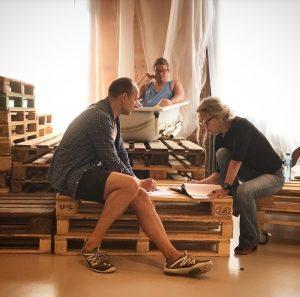 Jan och Nina sitter på lastpallar och läser manus, bakom dem sitter Ronnie i ett badkar.