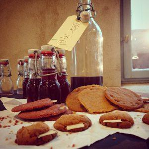 Små kakor med lappar i samt flaskor med röd dryck. Runt en flaskhals sitter en lapp med texten Drick mig.