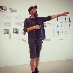 Scenograf Ilkka pekar i rummet, på väggen bakom honom sitter skisser och inspirationsbilder.