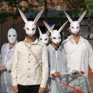 Fem skådespelare i kaninmask tittar rakt in i kameran, en håller i en kundvagn.